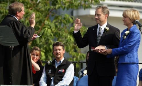 Outgoing Alaska Governor Sarah Palin (2nd L), her husband Todd (C) look on as incoming Governor Sean Parnell (2nd R) is sworn in by Supreme Court Justice Daniel Winfree (L) during the annual Governor's Picnic July 26, 2009 at Pioneer Park in Fairbanks, Alaska. Parnell' wife Sandy held the bible for the ceremony. Craig E. Campbell was sworn in as the new Lieutenant Governor.