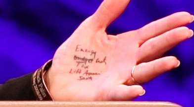 The crib notes in questions on the palm of Sarah Palin's hand.